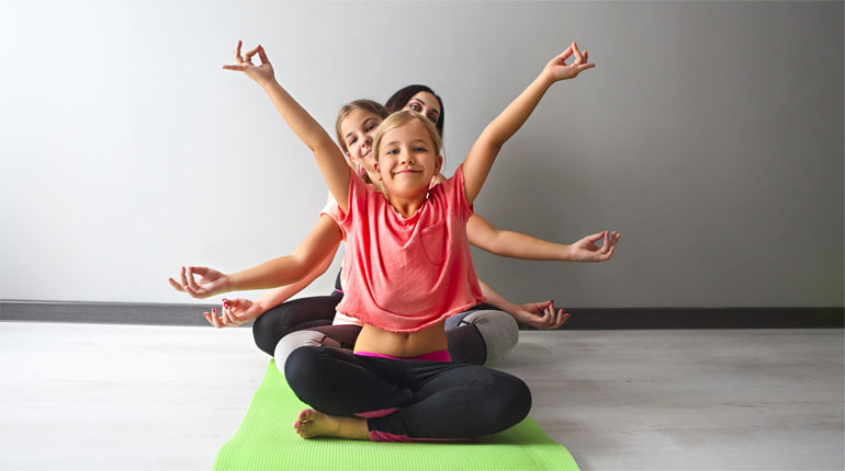 Young woman having fun with kids doing yoga. Family sport concept © AdobeStock